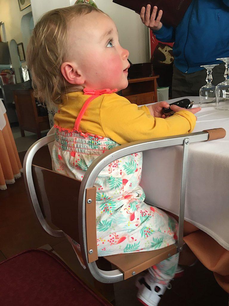 Onze dochter in een Portugese kinderstoel in een restaurant